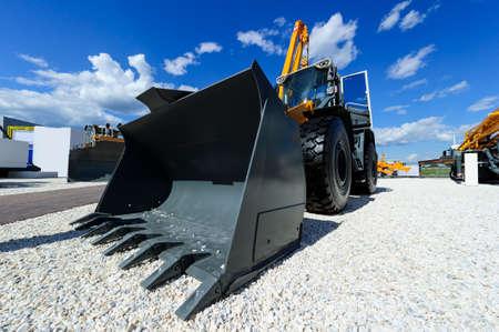 Loader, Rad-Bulldozer mit großen grauen Eimer, Baugewerbe, schwere gelbe Bagger auf Baugebiet mit Kies, Maschinen, blauer Himmel und weißen Wolken im Hintergrund