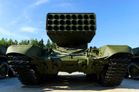 ballistic: Multiple missile launcher, military industry, heavy mobile flamethrower system among two armored personnel carriers, green thermobaric ballistic weapon complex, modern army, blue sky on background Stock Photo
