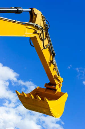 Excavator bucket, bulldozer shovel, hydraulic piston system of yellow construction vehicle isolated on blue sky with white clouds