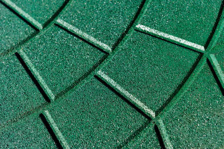 crumb: Textured rubber crumb artificial coating of green color, product of used old tires, waste recycling industry, selective focus