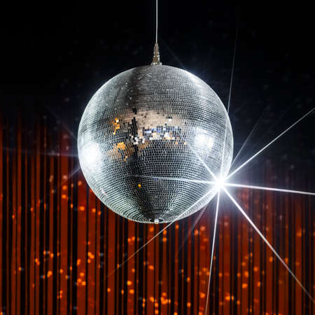 entertainment background: Disco ball with stars in nightclub with striped orange and black walls, party and nightlife entertainment industry