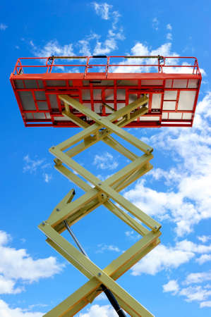 Scherenhebebühne mit Hydrauliksystem auf maximale Reichweite Höhe in orange und beige lackiert, große Baumaschine, Schwerindustrie, weißen Wolken und blauem Himmel im Hintergrund