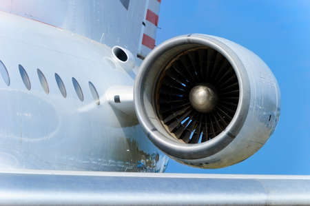 Engine on white fuselage with portholes of passenger plane, jet turbine, windows, hull and wing, aircraft detail, aviation and aerospace industry, blue sky on background