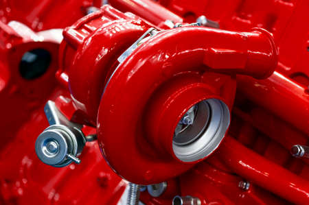 oversize: Turbocharger of red powerful engine, turbine of diesel motor for oversize trucks, SUV, cargo, commercial and construction vehicles, heavy industry, detail