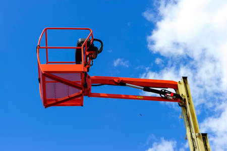 construction vehicle: Hydraulic lift platform with bucket of construction vehicle painted in orange and beige colors with white clouds and blue sky on background
