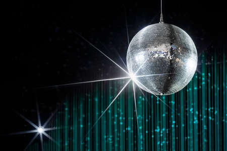 Disco ball with stars in nightclub with striped turquoise and black walls lit by spotlight, party and nightlife entertainment industry