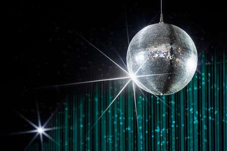 Disco-Kugel mit Sternen in Nachtclub mit gestreiften Türkis und schwarzen Wänden beleuchtet von Spotlight, Party und Nachtleben Entertainment-Industrie