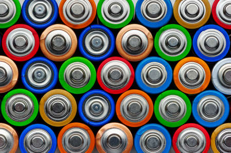 Batterijen, bovenaanzicht, rijen van alkaline batterijen AA-formaat in groen, rood, blauw, brons, goud, oranje, kleuren, energie abstracte achtergrond Stockfoto