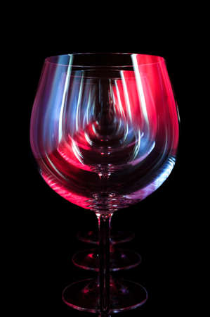 wine glass: Party wine glasses in nightclub lit by red, blue, lilac lights, nightlife and entertainment industry, objects in row isolated on black background