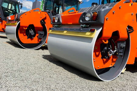 Steamroller, heavy road roller and vibration roller compactor in row on grey gravel, construction industry, blue sky and white clouds on background Standard-Bild
