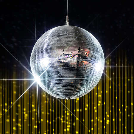 yellow walls: Party disco ball with stars in nightclub with striped yellow and black walls lit by spotlight, nightlife entertainment industry Stock Photo