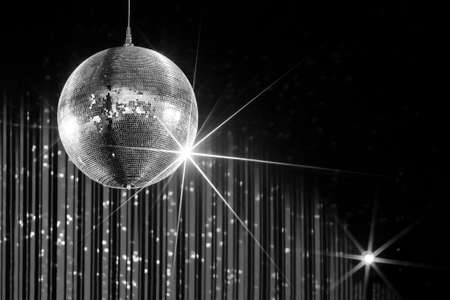 Party disco ball with stars in nightclub with striped walls lit by spotlight, nightlife entertainment industry, monochrome