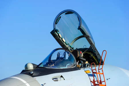 modern fighter: Fighter jet with open empty bulletproof cockpit of military multifunction plane, fourth-generation aircraft, modern army industry, supersonic air force, blue sky on background, selective focus