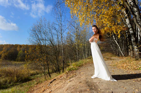 girl pose: Young beautiful caucasian girl in white dress view in sunny colorful autumn forest with golden, bronze and green foliage, blue sky and white clouds on background Stock Photo