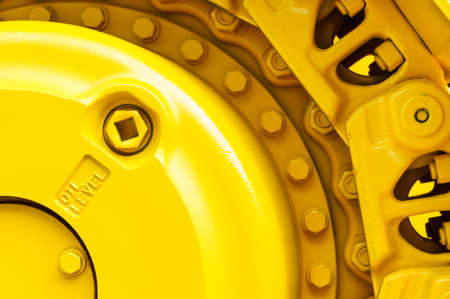 heavy: Track drive gear, bulldozer sprocket mechanism, large construction machine with bolts and yellow paint coating, heavy industry, detail