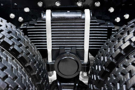 oversize: Leaf spring with four tires of commercial truck, black suspension with chrome nuts and bolts for oversize vehicles, SUV, cargo and construction mode of transports, heavy industry, detail Stock Photo