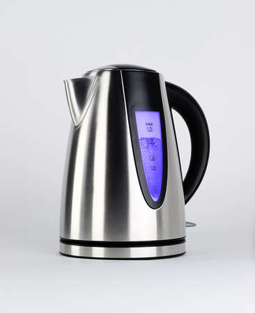 electric tea kettle: Steel electric tea kettle with boiling water and blue backlight, isolated on white, studio shot