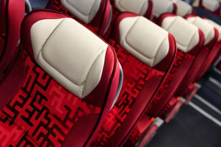mounts: Bus seats in row with red leather, textile coating, wooden armrests, white headrests and mounts for safety belts, modern comfortable tourist transport interior, selective focus Stock Photo
