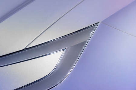 ultra modern: Car headlight, fender and hood in ultra modern style of powerful sport racing sedan with silver and violet aerodynamic bodywork, abstraction Stock Photo