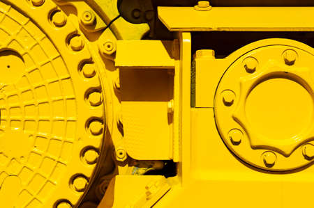 bulldozer: Track drive gear, bulldozer sprocket mechanism, large construction machine with bolts and yellow paint coating, heavy industry, detail
