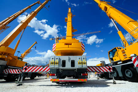 Mobile construction cranes with yellow telescopic arms and big tower cranes in sunny day with white clouds and deep blue sky on background, heavy industry Stock Photo