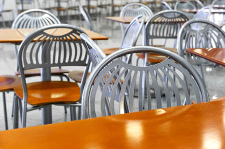 fast food restaurant: Chairs and tables in fast food restaurant, cafe silver steel furniture with orange wooden seats and working surfaces, food court, nutrition industry, selective focus