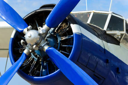 fuselage: Propeller of plane engine, vintage passenger biplane with fuselage of blue and white colors, retro aircraft, civil aviation, ready to start, blue sky on background