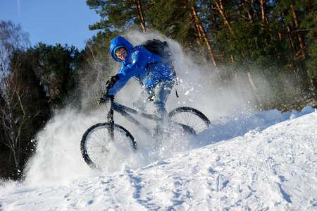 ciclismo: montar en bicicleta ciclista, ciclo invierno extremo cerca de los bancos de nieve ladera de la montaña de nieve, esquí de fondo en bicicleta cerca del bosque en un día soleado fresco