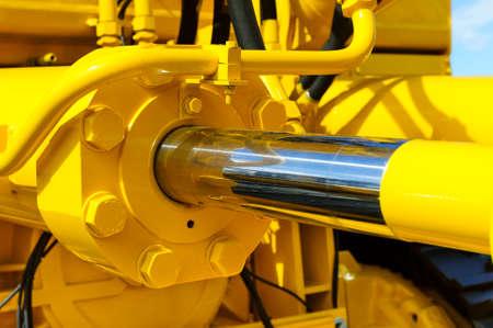 pistone idraulico per ruspe, trattori, escavatori, cromato dell'asse del cilindro della macchina di colore giallo, l'edilizia pesante dettaglio, messa a fuoco selettiva