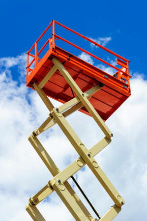 scissor: Scissor lift platform with hydraulic system at maximum height range painted in orange and beige colors, large construction machine, heavy industry, white clouds and blue sky on background
