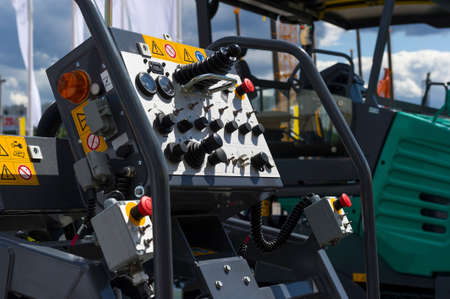 asphalt paving: Control panel of asphalt paving machine, heavy industry, dashboard unit with buttons, levers, toggle switches, knobs, signal lights, sensors, indicators and handles, road construction machines on background Stock Photo