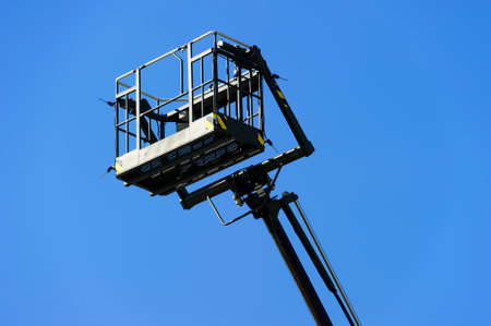 construction vehicle: Hydraulic lift platform with bucket of construction vehicle painted in black color with blue sky on background
