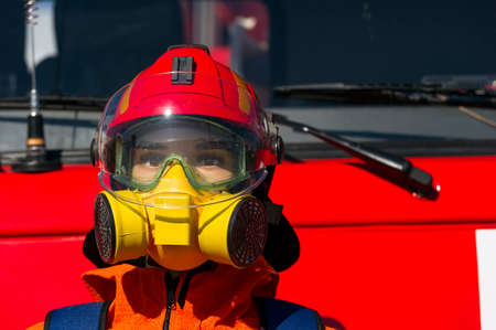 safety goggles: Firefighter hard hat, breathing mask or respirator with interchangeable filter cartridges and safety goggles on mannequin with red fire-fighting truck on background, fireman protective means, rescue service