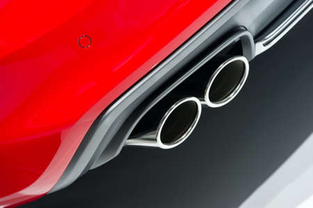 bodywork: Chrome exhaust pipes of powerful sport car with red bodywork and grey bumper