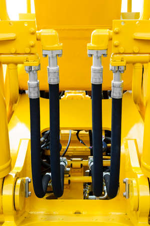 hydraulic hoses: Hydraulic hoses and steel connectors for bulldozers, tractors, excavators and loaders, four, rubber tubes with screws and bolts of yellow machine, construction heavy industry detail