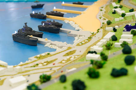 green military miniature: Warships wharf scale model, layout of army naval base, miniature of military harbor with small models of ships, piers, docks, buildings and port driveways, selective focus Stock Photo