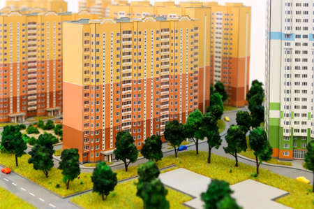 prefabricated buildings: Apartment buildings scale model, residential district layout, mock-up of colorful prefabricated houses with childrens playground, trees, grass, roads, sidewalks, driveways, selective focus