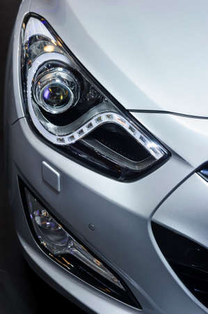 silver sports car: Car headlight, hood and bumper with plastic air intake of powerful sports car with silver metallic glossy bodywork Stock Photo