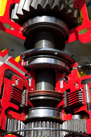 sprockets: Bulldozer drive gear mechanism cross section, sprockets, bearings, bolts of diesel engine, large construction machine with red and yellow paint coating, heavy industry, detail Stock Photo