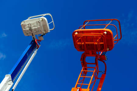 construction platform: Lift platform with bucket and articulating boom with basket of construction hydraulic telescopic cranes, orange and white cherry picker aerial work platforms, heavy industry, blue sky on background