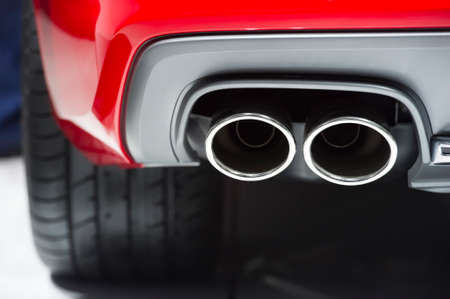 chrome: Chrome exhaust pipes of powerful sport car with red bodywork and grey bumper