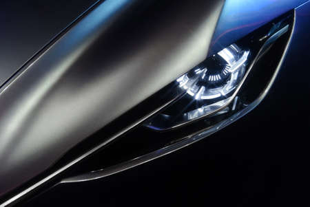 xenon: Predatory car headlight and hood of powerful sports grey car with blue glare on dark background