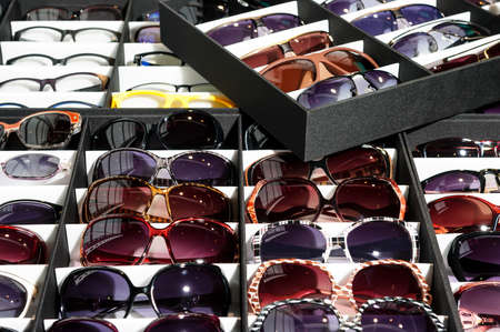 protective eyewear: Many sunglasses, wide range of protective eyewear lying in the grey and white boxes, selective focus