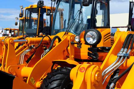 aparatos electricos: faros bulldozer, fila de máquinas enormes naranja potentes de construcción, tractores, excavadoras, se centraron en centro de atención, la industria pesada, cielo azul y nubes blancas sobre fondo