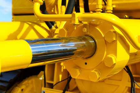 Hydraulic piston system for bulldozers, tractors, excavators, chrome plated cylinder shaft of yellow machine, construction heavy industry detail, selective focus