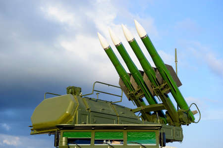 Missile launcher with four ballistic missiles ready to attack and radar on top of army transportation, antiaircraft forces, military industry, blue sky and clouds on background