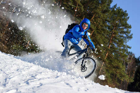 Cyclist riding bike, extreme winter cycling near snowbanks of snowy mountain slope, cross country biking near forest in cool sunny day Stock Photo