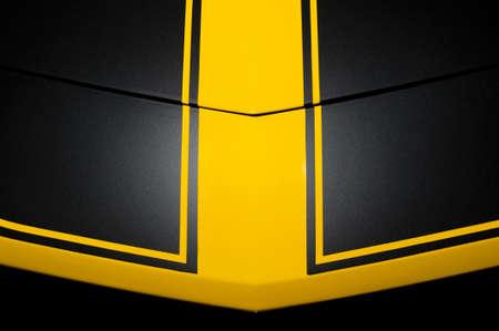 bodywork: Surface of black sport sedan car, metal hood with yellow arrow lines, part of vehicle bodywork Stock Photo