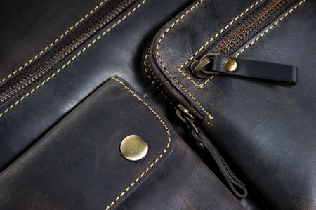 clutch cover: Leather bag with zipper, magnetic clasp on pocket and stitches, mens accessories in vintage style, macro shot, selective focus