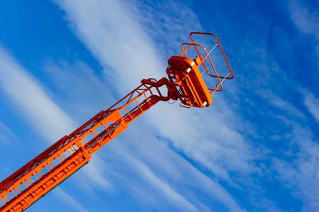 hydraulic lift: Hydraulic lift platform with bucket of orange construction vehicle, heavy industry, blue sky and white clouds on background